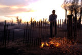 TUESDAY APRIL15TH, 2008  Ross Barrett tries to put out a smoldering fire on a fence that belonged...