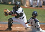 Bears catcher Erik Whinery, waits for the ball while Patriots player, Ryan Goins,  slides safely...