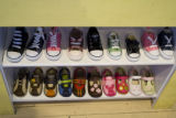 "A virety of little shoes that resemble ""big people's"" shoes line the shelves at Real..."