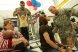 MJM135  Brian Wright (cq), top, swings his son, Nolan Wright, 2, as Srgt. Nick Cornelius (cq),...