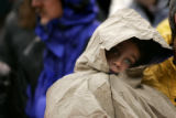 A fan huddles in his poncho in the rain in the second quarter of the Denver Broncos against the...
