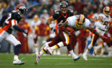 Denver Broncos Marques Anderson(left) and John Lynch chase a stumbbling  Washington Redskins...