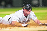 Rockies Matt Holliday slides into third after hitting a triple in the bottom of the 8th inning,...
