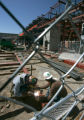 BG0078 Welders work on the new Courtyard Lofts, left, at Cherry Creek North in Denver Colo.,...