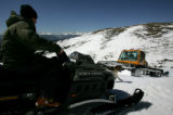 Michael Coors rides a snowmobile as a cat cuts a trail on land he wants to open skiers at his...