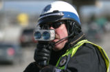 Denver Police Technician Kevin Smolka uses a laser speed radar to clock driver's speed on...