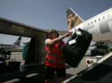 Shawn Stevens loads luggage onto Frontier's newest plane bound for Washington DC at DIA in Denver,...