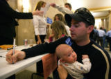 Larry Behrendt  (q) holds his baby Logan Behrendt as he signs up to speak in favor of maintaining...
