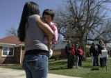Marisol Bolanos (cq) holds her daughter Nayeli Lopez, ten months, while Mairsol's husband...