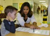 First grade student Noah Perez is helped by Martina Perez (cq), left to right - no relations, with...