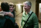 Kate Burns, center, is hugged by friend and supporter Frederique Chevillot  as Sheila Schroeder,...