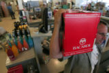 Brad Knapp carries out liquor for a customer at Applejack Liquor  Store in Wheatridge  Monday...