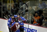The Colorado Avalanche's Patrice Brisebois (#71) celebrates with teammates Alex Tanguay (#18) and...