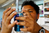 Christian Quezada, 13, carefully hangs a soda can on the metal mobile sculpture he's making during...