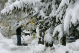 George Karklins (cq) shovels snow in front of the Hamlet's Book Shoppe, on main Street in...