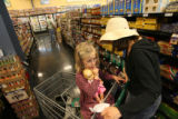 MJM040  Thea Hunter, 5, sits in a shopping cart with her doll as her mother, Stephanie Hunter...