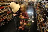 MJM056  Thea Hunter, 5, sits in a shopping cart with her doll as she and her mother, Stephanie...