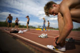 Pete Janson (cq) ties his shoe during track practice at Potts Field in Boulder. Janson, who was...