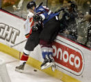 The Colorado Avalanche's Ossi Vaananen (#27) goes airborne while checking the Calgary Flames' Eric...