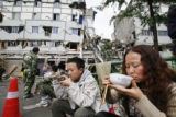 TOK805 - Earthquake survivors eat while rescue workers rest by damaged buildings in Dujiangyan,...