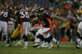 Denver Broncos quarterback Jay Cutler hands off the ball in the first quarter as the Denver...