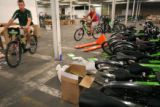 (047) Volunteers and members of Humana and Bikes Belong Coalition ride bikes through a warehouse...