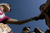 Kaitlin Mahoney, 23, of Washington, D.C., left, grabs her bible back from Jay Becker, of Chicago,...