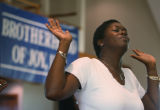 Margaret VanValen listens to the praise team before Rev. Al Sharpton preaches at the House of Joy...