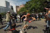 A protester who refused to give his name shakes his backside at police in riot gear on Broadway in...