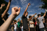 Brandon Pulling, 20, of Denver, holds up a fist with other protesters during a rally at the State...