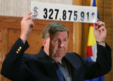 Douglas Bruce, El Paso county commissioner, holds up a number that he says is the total cost of...