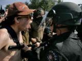 A protesters scream and confront law enforcement officers as they create a blockade during an...