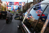 (148) Fifty state flags flap in the breeze and some reflect in the window of a car in thick trafic...