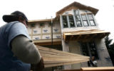 Construction workers Jeff Strub (cq) left and Jason Fittje (cq) carry lumber at a large remodel on...