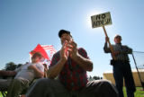 (121)   Jim Haas, left, and Dana Isham, center,  both of Grand Junction listen in to a speach...