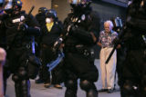 Police remove Cecil Bethea, 80, from a circle of protesters after he got caught in the march while...