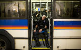 An Aurora police officer rests on a bus in downtown Denver after the first night on the Democratic...