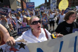 Hillary Clinton supporter Sharon Pucker of South Dakota marches down Colfax Ave. during the...