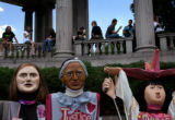 (PG4387) People watch a rally at Civic Center Park where puppets made by Code Pink Taos rest...