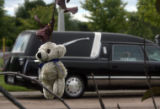 A small teddy-bear hangs from a tree near the site were family and friends gathered to bury the...