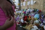 Michelle Ramirez, 7, (cq) holds her father Alfredo's (cq) hand while looking at a memorial of...