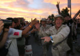 Former Unites States armed forces men and women celebrate after one of Obama's liaisons, responded...