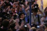 A throng of photojournalists follow Sen. Hillary Rodham Clinton  through the crowds on the floor...