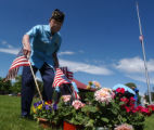 (DENVER COLO., May 31, 2004 )  Harry Nakagawa  puts  a flag on a grave site at Fairmount Cemetery...