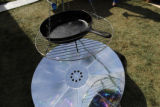 A solar mirror reflects onto a frying pan as part of a sloar cooking display at Photovoltaic Fun...