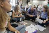School Review Team member Pat Termin (cq, right center), a retired teacher and principal, listens...