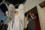 Dressed as an angel, Carrie Jackson, 26, of Boulder, is video taped by John Martin , of Denver,...