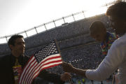 Danny Lopez of Denver hands a flag back to Brenda Munford(cq) of Cleveland OH., and her grandson,...