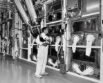 Rocky Flats employee handles a robotic arm assembly in conjunction with an--text marked out-- ...