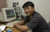Kent Shiao, (cq), Network Technician, works at his desk demonstrating a remote into a firewall....
